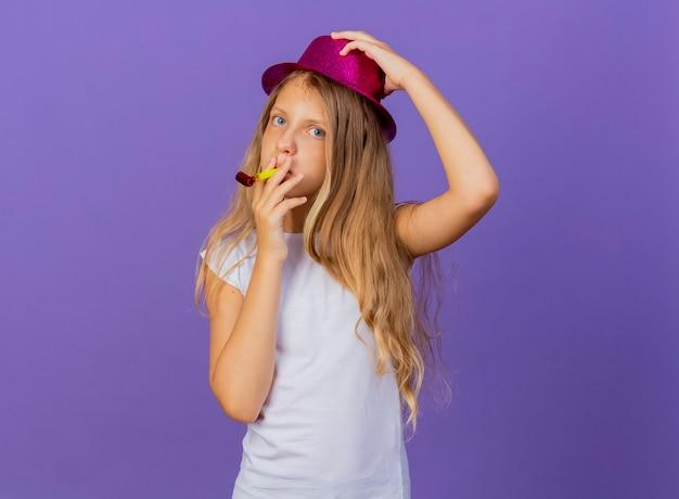 Mooi klein meisje in vakantie hoed blaast fluitje blij en positief, verjaardagsfeestje concept permanent over paarse achtergrond