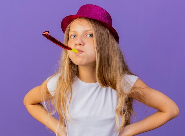 Mooi klein meisje in vakantie hoed blaast fluitje ontevreden