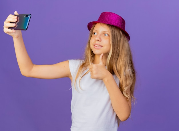 Mooi klein meisje in vakantie hoed doet selfie met smartphone glimlachend duimen opdagen, verjaardag partij concept staande over paarse achtergrond