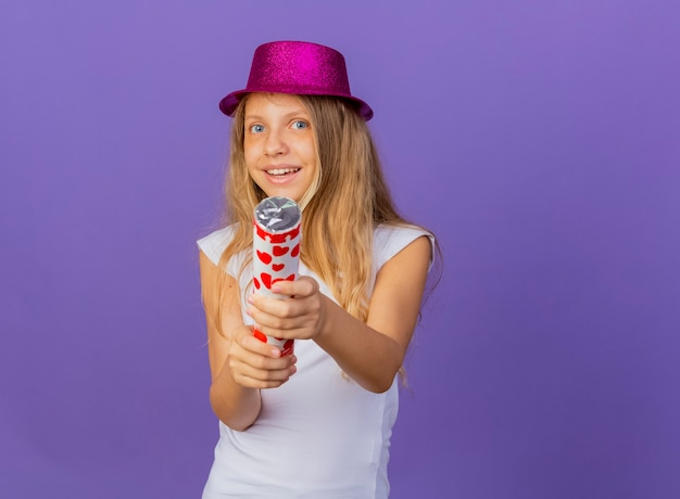 Mooi klein meisje in vakantie hoed houden partij cracker blij en opgewonden, verjaardagsfeestje concept permanent over paarse achtergrond