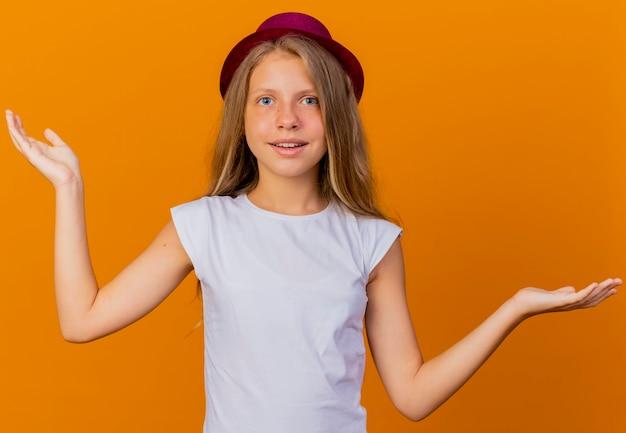 Mooi klein meisje in vakantie hoed kijken camera glimlachend spreidende armen naar de zijkanten, verjaardagsfeestje concept permanent over oranje achtergrond