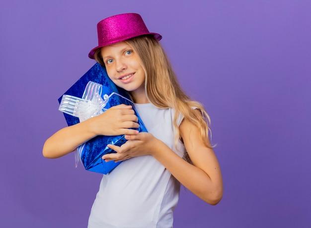 Mooi klein meisje in vakantie hoed knuffelen geschenkdoos camera kijken met blij gezicht glimlachen, verjaardagsfeestje concept permanent over paarse achtergrond