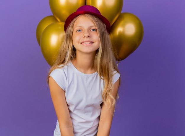 Mooi klein meisje in vakantie hoed met bos van baloons lookin camera glimlachen vrolijk blij en positief, verjaardagsfeestje concept staande over paarse achtergrond