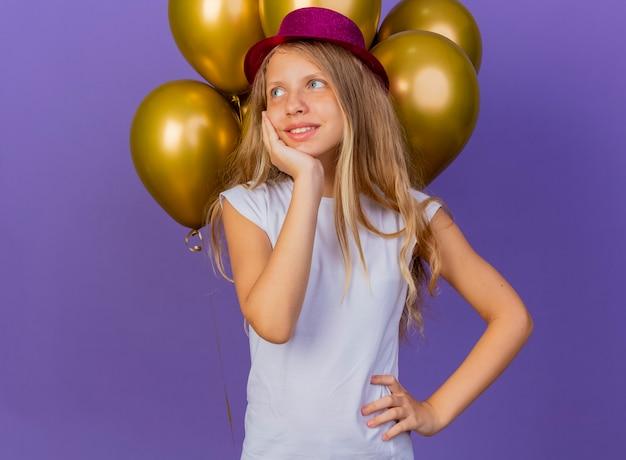 Mooi klein meisje in vakantie hoed met bos van baloons opzij kijken met blij gezicht gevoel positieve emoties glimlachen, verjaardag partij concept staande over paarse achtergrond