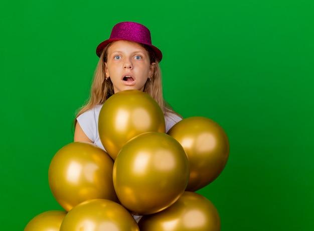 Mooi klein meisje in vakantie hoed met bos van baloons opzij kijken verbaasd en verrast, verjaardagsfeestje concept staande over groene achtergrond