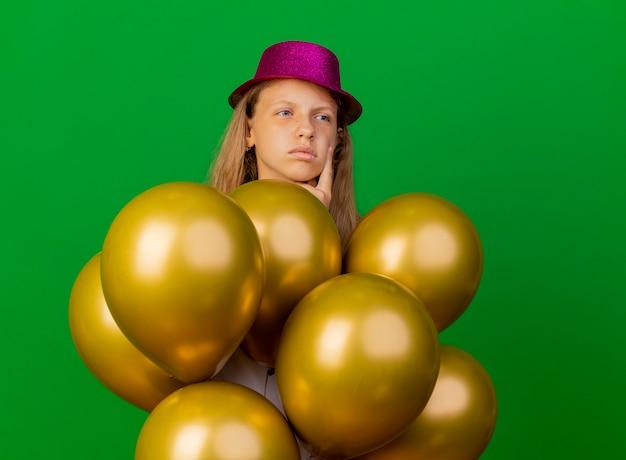 Mooi klein meisje in vakantie hoed met bos van baloons opzij kijken verbaasd, verjaardagsfeestje concept staande over groene achtergrond