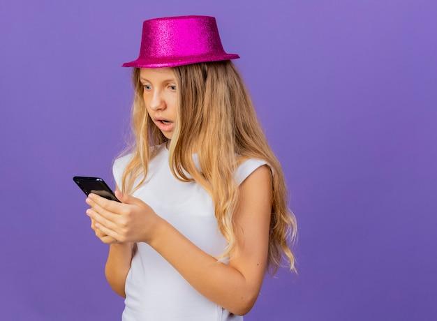 Mooi klein meisje in vakantie hoed met smartphone wordt verbaasd en verrast, verjaardagsfeestje concept permanent over paarse achtergrond