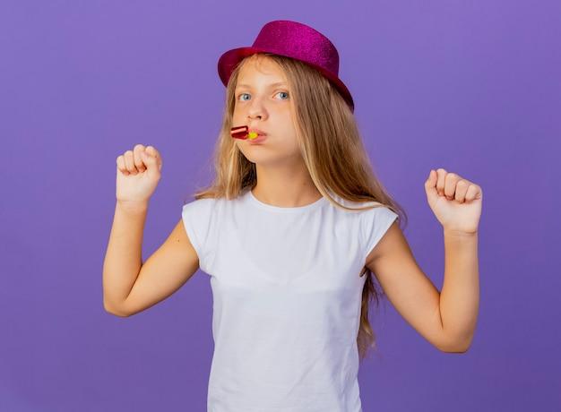 Mooi klein meisje in vakantie hoed waait fluitje balde vuisten blij en opgewonden, verjaardagsfeestje concept permanent over paarse achtergrond