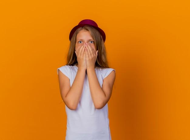 Mooi klein meisje in vakantiehoed die geschokt is over de mond met handen, verjaardagsfeestje concept