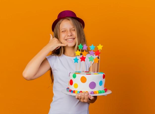Mooi klein meisje in vakantiehoed met verjaardagstaart glimlachend en bel me gebaar, verjaardagsfeestje concept
