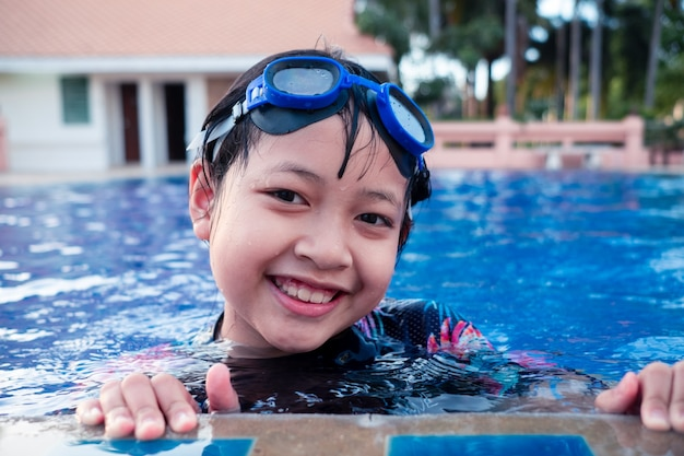 Mooi klein meisje in zwembad met glimlach en gelukkig in de zomer