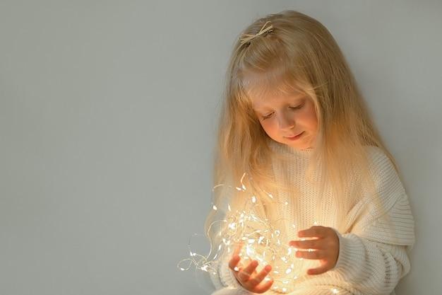 Mooi klein meisje kijkt neer op de kerstverlichting in haar handen