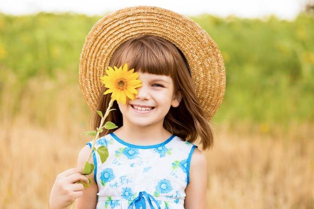 Mooi klein meisje lacht en verbergt oog met zonnebloembloem die buiten loopt in de voorjaarsvakantie