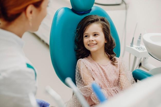 Mooi klein meisje lacht tijdens een gesprek met haar pediatrische stomatolgist voordat ze tanden onderzoek doet.