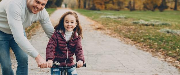 Mooi klein meisje leren fietsen met haar vader buiten in het park.