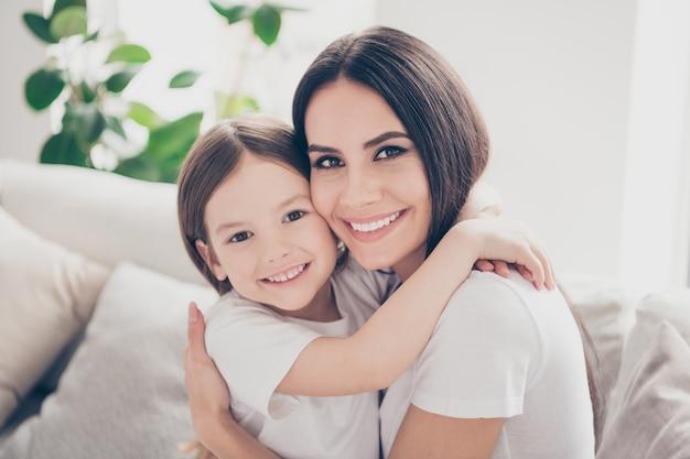 Mooi klein meisje, leunende wang naar jonge mama haar in huis huis binnenshuis omhelzen