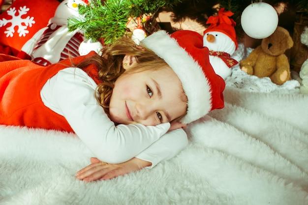 Mooi klein meisje ligt voor een kerstboom