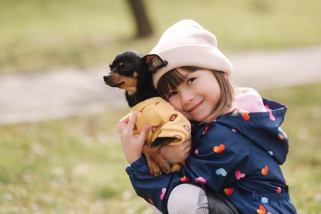 Mooi klein meisje lopen met schattige hond buiten zes jaar oud meisje knuffel haar huisdier