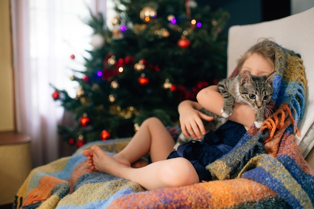 Mooi klein meisje met blond haar in blauwe jurk houdt haar mooie speeltje en zit in de babykamer in een fauteuil en glimlacht