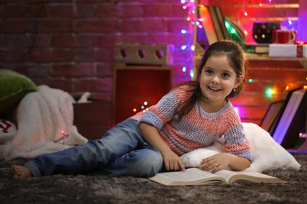 Mooi klein meisje met boek in met kerst versierde kamer
