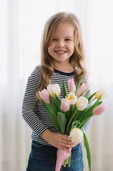 Mooi klein meisje met een bos van tulpen op een happy mothers day. maakt een geschenk voor haar moeder.