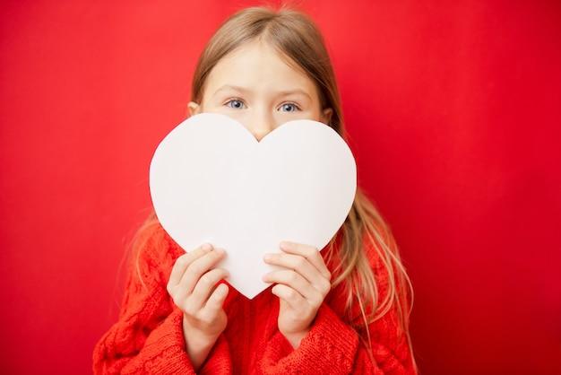 Mooi klein meisje met een groot hart van papier, op rode achtergrond