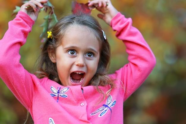 Mooi klein meisje met grote ogen maken gezichten