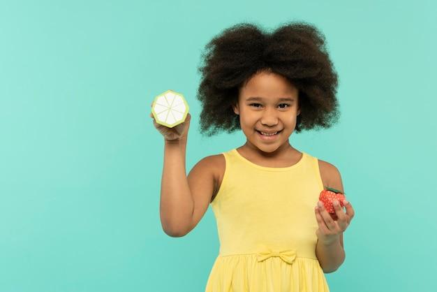 Mooi klein meisje met plezier in een zomer instelling studio