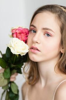 Mooi klein meisje met roze roos, klein mooi meisje in roze houdt het boeket rozen vast. sluit de bloemen en het gezicht