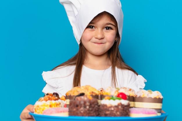 Mooi klein meisje met taarten en snoep