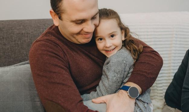 Mooi klein meisje omarmd door haar vader zittend op de bank thuis glimlachen.