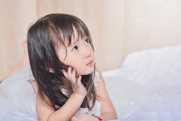 Mooi klein meisje op bed net opstaan en denken