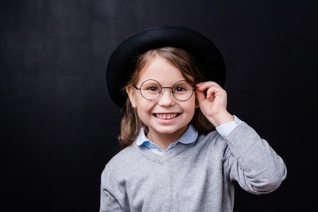 Mooi klein meisje op zoek naar jou met brede glimlach terwijl het aanraken van bril voor camera tegen zwarte ruimte