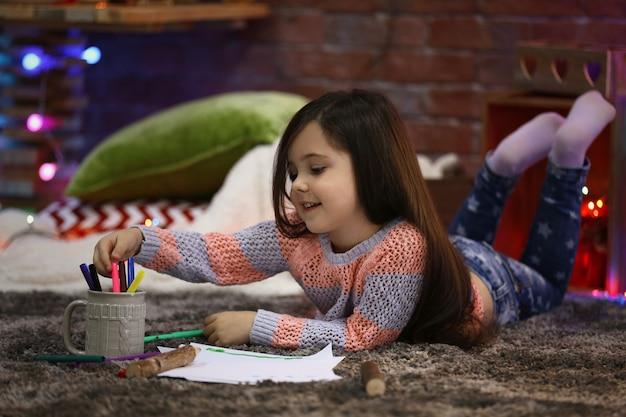 Mooi klein meisje schilderen in een met kerst versierde kamer