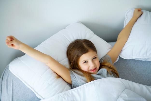 Mooi klein meisje slaapt thuis in bed, moeder bedekt haar met een dekbed