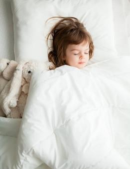 Mooi klein meisje slapen in wit bed met konijn speelgoed in de buurt van haar