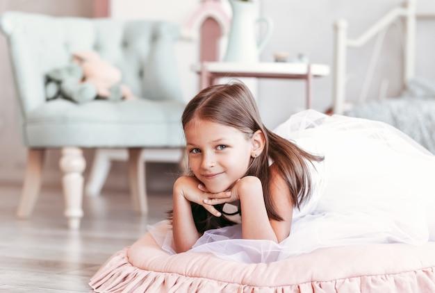Mooi klein meisje speelt in de lichte kamer. portret van een gelukkig kind