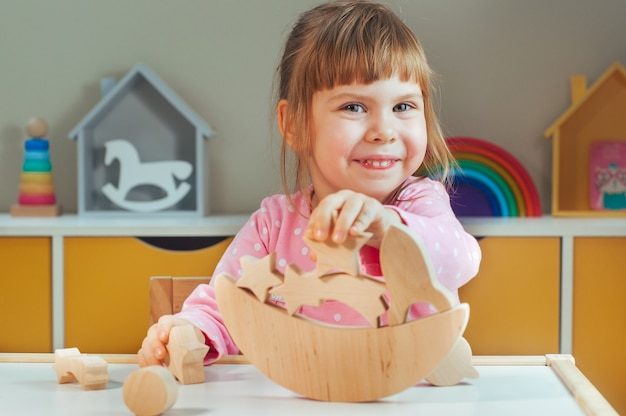 Mooi klein meisje speelt met houten speelgoed galaxy balancer op tafel in de kinderkamer