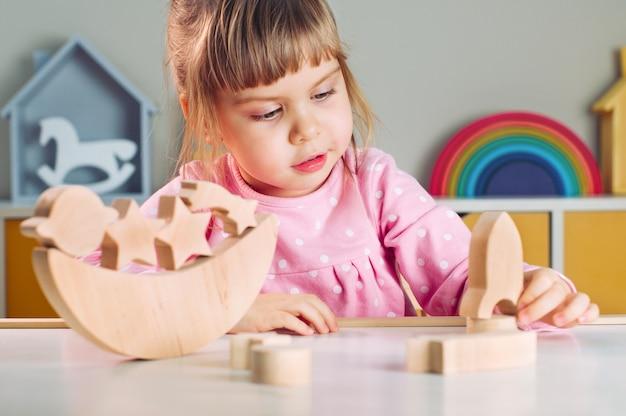 Mooi klein meisje speelt met houten speelgoedraket van galaxy balancer op tafel in de kinderkamer