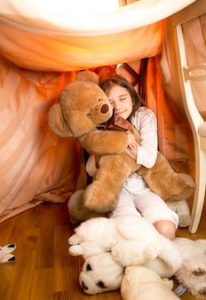 Mooi klein meisje speelt met teddybeer in zelfgemaakt huis