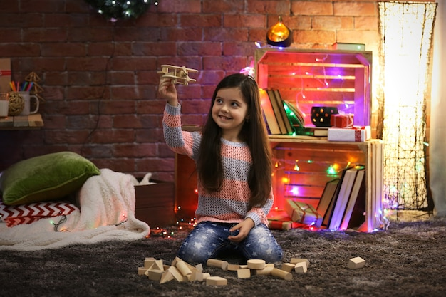 Mooi klein meisje spelen met houten vliegtuig in kerst ingerichte kamer