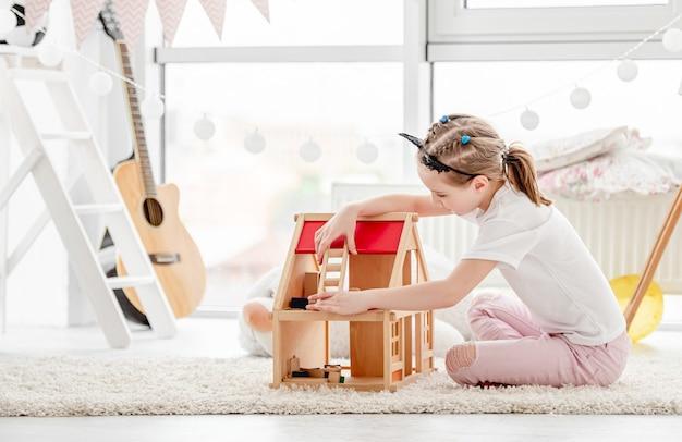 Mooi klein meisje spelen met poppenhuis