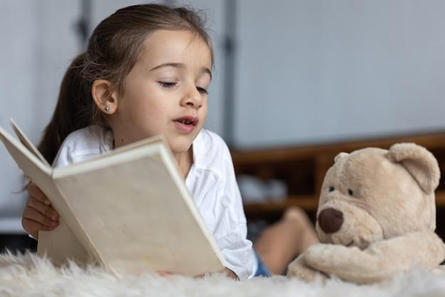 Mooi klein meisje thuis, liggend op de vloer met haar favoriete speeltje en leest een boek.