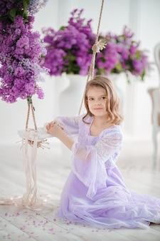 Mooi klein meisje van voorschoolse leeftijd in een delicate jurk zittend op een schommel versierd met lila bloemen