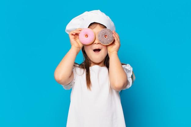 Mooi klein meisje verraste uitdrukking. koken snoep concept