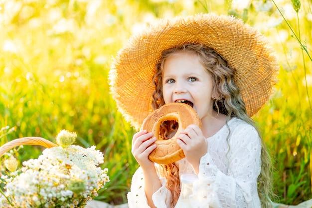 Mooi klein meisje, zittend in een strooien hoed in een geel veld met wilde bloemen met een fles melk en een bagel, picknick in het veld