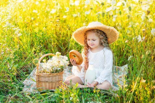 Mooi klein meisje, zittend in een strooien hoed in een geel veld met wilde bloemen met een fles melk en een bagel