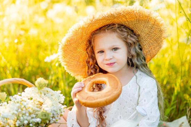 Mooi klein meisje, zittend in een strooien hoed in een veld en het eten van een bagel, picknick in een veld