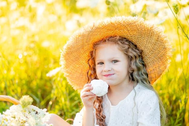 Mooi klein meisje, zittend in een strooien hoed in een veld en marshmallows eten