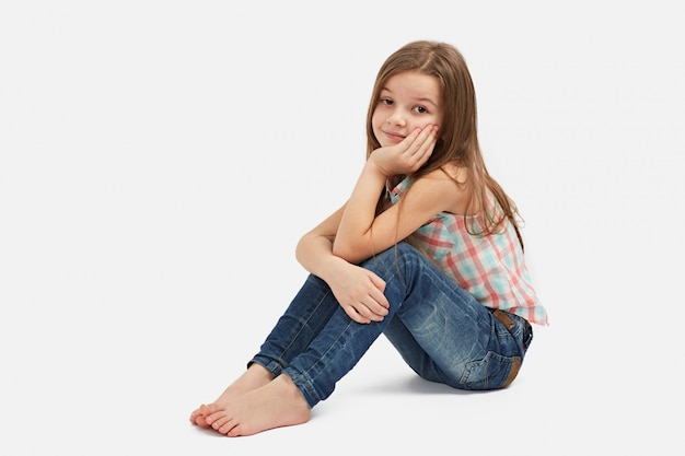 Mooi klein meisje, zittend op de vloer